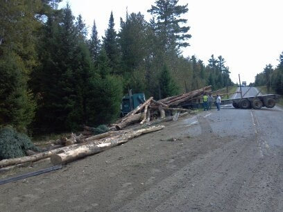A tractor-trailer involved in a collision with a pickup spilled tree-length logs onto Route 11 shutting down one lane for several hours Tuesday morning in Township 9, Range 5 in Aroostook County. No injuries were reported, according to state police.