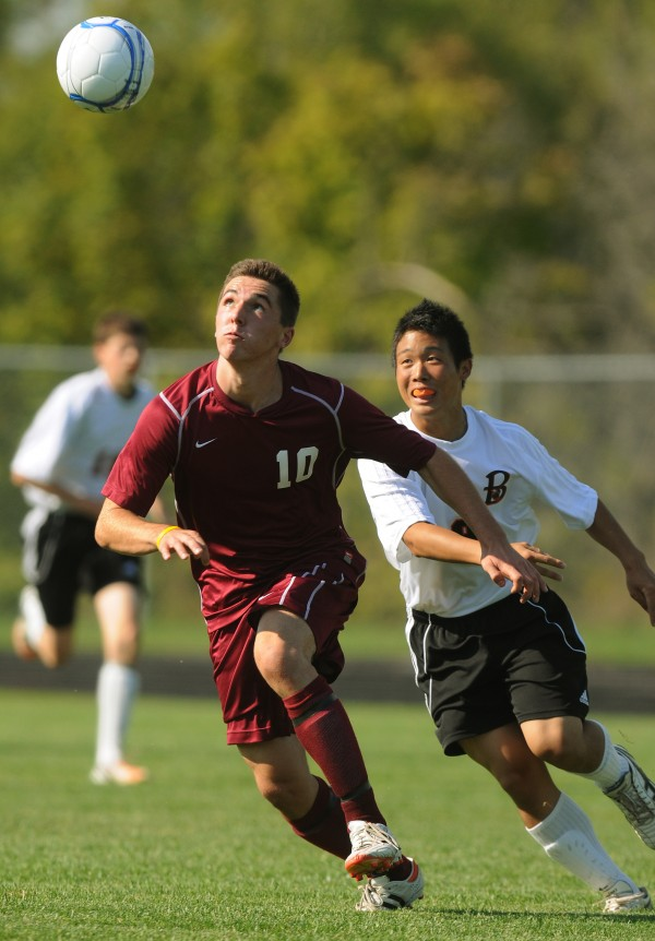 Bangor's Dominic Veilleux (left) and Brewer's Yutaro Kawanura chase down a ball during the first half of a soccer game on Friday, september 7, 2012, in Brewer. Bangor won 4-1.