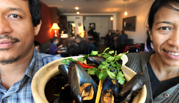 Ravin Nakjaroen (left) and his wife, Paula Palakawong, carry a bowl of Pemaquid mussels in spicy coconut lemongrass broth. As co-owners of Long Grain restaurant in Camden, they serve home-cooked Asian street foods.