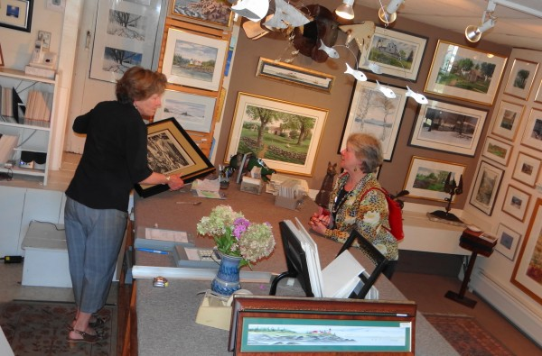 Kathy Valente (left), co-owner of Small Wonder Gallery in Camden, helps customer Liz O'Loughlin find an etching. O'Loughlin, who is visiting the East Coast from her home in Australia, is staying with a friend in Belfast.