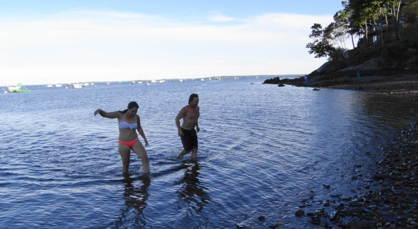 Sigrid Coffin and Dan Greeley walk to shore after submerging in Penobscot Bay near the Belfast Boat House. The friends pledged to swim every day from June 20 to Sept. 22.