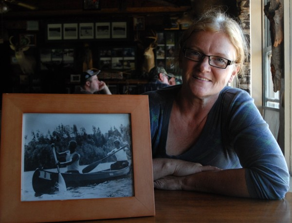 Darlene Kelly Dumond talks about the Old Town Canoe given to her father, Tyler Kelly, and his cousin Ransford Kelly after they used it in the Fort Kent Centennial Canoe Race from Allagash to Fort Kent on the St. John River in 1969. The two men are pictured in that canoe, which was stolen on or around Aug. 12 from Allagash. The reward for any information leading to its recovery is up to $250 and a gallon of gin.