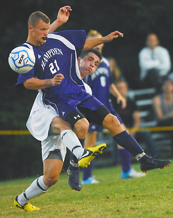 Hampden's Tristan Gardner (21) puts a shoulder on the ball in front of Bangor's Dominic Veilleux (10) in first-half action at the Bangor High School soccer field Thurday, Sept. 13, 2012. The game ended in a 2-2 tie.