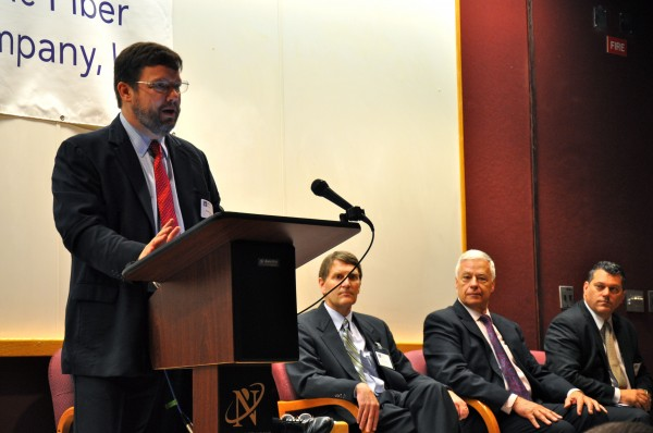 Fletcher Kittredge, CEO of Biddeford-based GWI, speaks at an event in Brunswick celebrating the completion of the Three Ring Binder project, which he was instrumental in launching. In the background are, from the left, Dwight Allison, CEO of Maine Fiber Co.; U.S. Rep. Mike Michaud; and George Gervais, commissioner of the Department of Economic and Community Development.