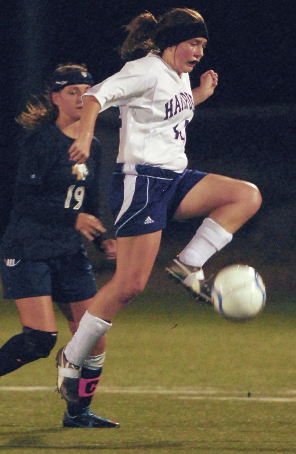 Hampden Academy's Alex Winchester (14) leaves the ground to control the ball ahead of Mt. Blue Academy's Makenzie Thompson (19) during second-half action at Hampden Academy on Tuesday evening, Sept. 18, 2012.