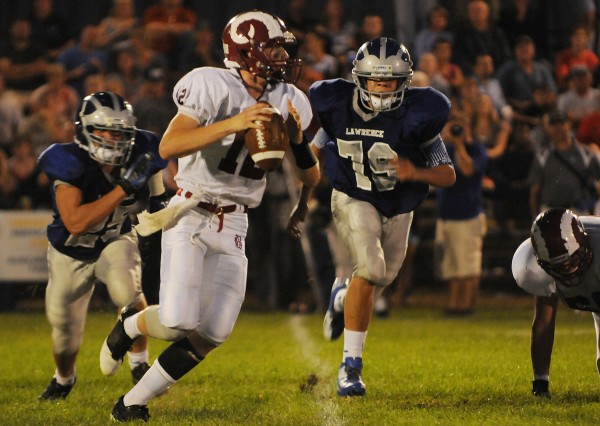 Bangor quarterback Carl Farnham looks for a receiver while being pursued by Lawrence defenders Jake Doolan (25) and Trevor Hamblet (79) during 2nd quarter action on Friday, September 7, 2012, at Lawrence.
