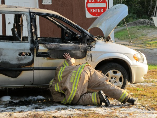 Ellsworth Fire Lt. Ken Worden inspects the undercarriage of a 2002 Dodge Caravan that mysteriously burst into flames Wednesday evening, Sept. 12, 2012 on Red Bridge Road. Worden said it's unclear what caused the blaze.