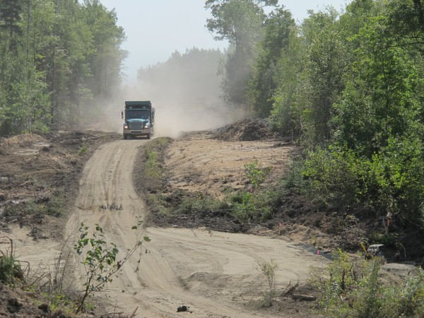 A dump truck drives down an unfinished stretch of Route 180 under construction in Ellsworth. The new road will reroute 180, connecting it directly with Route 1A and eliminating the need for a failed bridge at Graham Lake Dam.