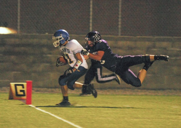 Belfast's Tyler Tran (21) manages to cross the goal line before Hampden's Matt Haws (3) brings him down in first-period action at Hampden on Friday evening, Sept. 21, 2012.