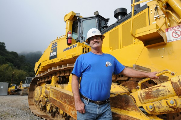 Allen Black, 49, a laid-off heavy-machinery operator from Staffordsville, Ky., stands alongside a Komatsu 375 bulldozer at Brandeis, a local sales and service operation in Stanville, Ky., on Aug. 30.