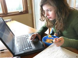 In this Dec. 3, 2009 photo, Maria Vespa eats a macaroni and cheese lunch while working on her geography test at home, in Duluth, Minn. Vespa and her sister Anna both attend a &quotvirtual school&quot where they take all their classes online.