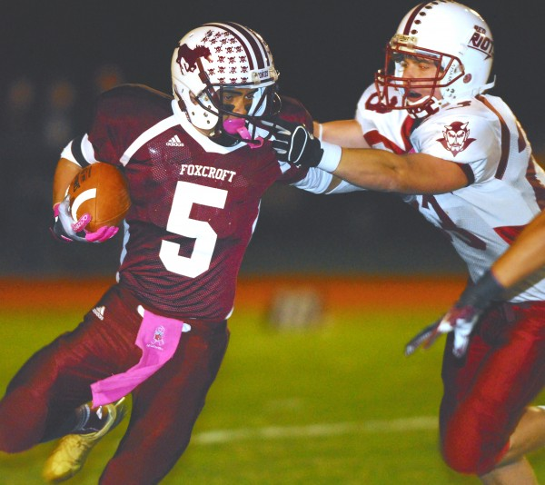 Foxcroft Academy's Ryan Rebar (5) battles to break free from Orono's Michael Fowler (23) during first-quarter action at Dover-Foxcroft, Friday, Sept. 28, 2012.