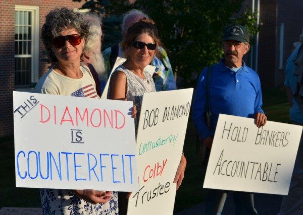 Several Occupy Augusta protesters hold signs during a demonstration outside the Diamond Building at Colby College in Waterville on Wednesday, Sept. 12, 2012.