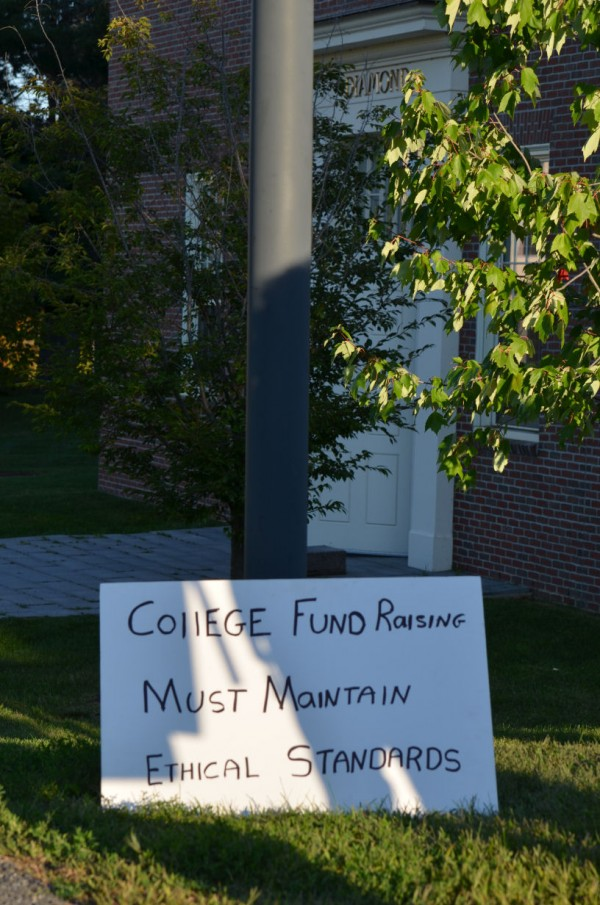 An Occupy Augusta sign leans against a pole with the Diamond Building entrance in the background at Colby College in Waterville on Wednesday, Sept. 12, 2012. Demonstrators picketed outside the building to ask the college to unseat board of trustees Chairman Bob Diamond.