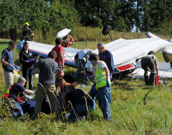 Emergency personnel attend to pilot Richard Bach after Bach's plane crashed in a field on Friday, Aug. 31, 2012, in Friday Harbor, Wash. Bach, the author of the 1970s best-selling novella &quotJonathan Livingston Seagull,&quot among other spiritually oriented writings often rooted in themes of flight, was in serious condition Sunday at Harborview Medical Center.