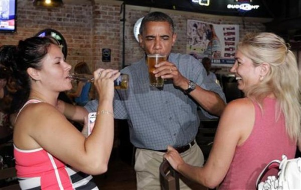 U.S. President Barack Obama enjoys a beer with Jennifer Klanac (L) and Suzanne Woods (R) at Ziggy's Pub in Amherst, Ohio July 5, 2012.