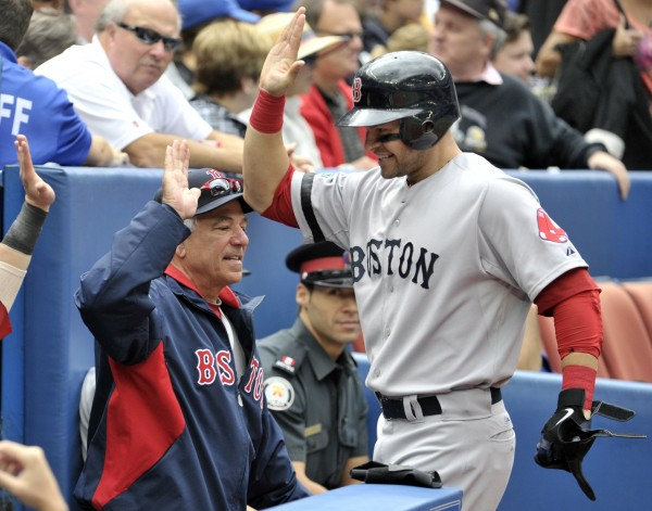 Boston Red Sox batter Cody Ross celebrates his home run beside manager Bobby Valentine during the second inning of their baseball game in Toronto Saturday, Sept. 15, 2012.