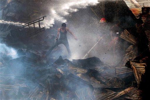 Bangladeshi firefighters and residents try to control a fire at the Begunbari slum in Dhaka, Bangladesh, Thursday, Sept. 20, 2012. The cause of the fire, in which at least 500 shanties were gutted, was not known.