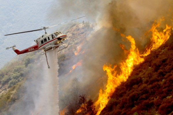 A Los Angeles County Firefighter helicopter drops water on a wildfire burning through 3,600 acres of the Angeles National Forest on Tuesday, Sept. 4, 2012 near Glendora, Calif. It could be a week before firefighters can contain the blaze because of high temperatures and rugged terrain in thick brush that hasn't burned in a couple of decades.