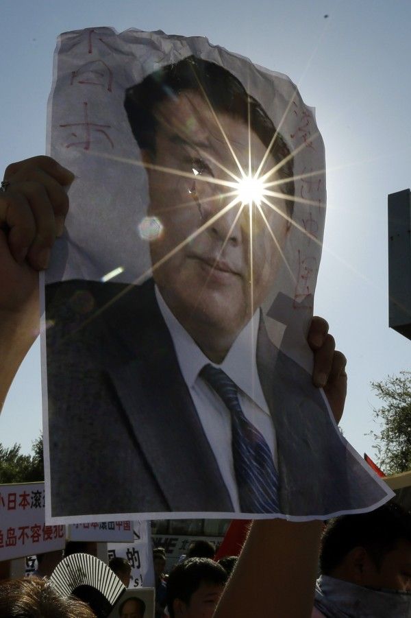 Sunlight shines through a hole cut out from the eye of a portrait of Japanese Prime Minister Yoshihiko Noda during a protest near the Japanese Embassy in Beijing, China on Tuesday, Sept. 18, 2012. The 81st anniversary of a Japanese invasion brought a fresh wave of anti-Japan demonstrations in China on Tuesday, with thousands of protesters venting anger over the colonial past and a current dispute involving contested islands in the East China Sea.