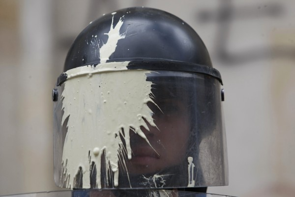 A riot police officer with his masked stained with paint thrown by students watches a march by teachers and students protesting a wide range of issues regarding the government's educational policies in Bogota, Colombia, Wednesday, Sept. 5, 2012.