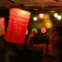 A girl touches a lantern at an outdoor restaurant during the Chinese Mid-Autumn Festival in Hong Kong Sunday, Sept. 30, 2012. Like ancient Chinese poets, Hong Kong people appreciate the beauty of the full moon in the Mid-Autumn Festival.