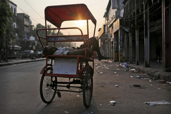 An Indian rickshaw puller sleeps on his bicycle in the street in New Delhi, India, early Wednesday, Sept. 12, 2012.