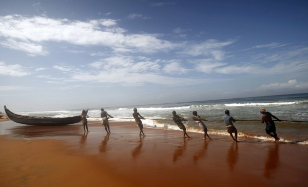 Indian fishermen pull a net they had laid to catch fish in the Arabian Sea in Trivandrum, India on Friday, Sept. 14, 2012.