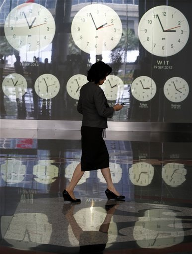 An Indonesian woman walks past clocks showing world time at the Jakarta Stock Exchange in Jakarta, Indonesia on Wednesday, Sept. 19, 2012.