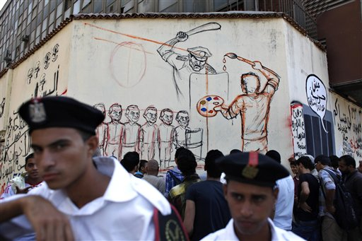 Two Egyptian policemen stand guard while Egyptian men gather by an artist working on a mural with faces depicting ousted Egyptian president Hosni Mubarak, on a newly whitewashed wall in Tahrir Square, Cairo, Egypt, Thursday, Sept. 20, 2012. Under cover of darkness, a few municipality workers quietly began to paint over an icon of Egypt's revolution: a giant, elaborate public mural on the street that saw some of the most violent clashes between protesters and police over the past two years. Arabic reads &quotpaint over the revolution, life standard, freedom, social justice.&quot