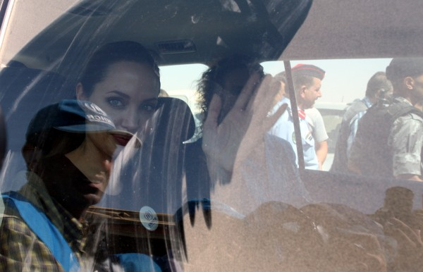 The U.N. refugee agency's special envoy, actress Angelina Jolie, waves through the dusty window of her car as she departs the Zaatari Refugees Camp in Jordan for Syrians who fled the civil war in their country Tuesday, Sept. 11, 2012. Jolie said Tuesday she heard &quothorrific&quot and &quotheartbreaking&quot accounts from Syrian refugees in a camp which hosts about 30,000 Syrians displaced by the 18-month conflict that has so far claimed at least 23,000 lives, according to activists.