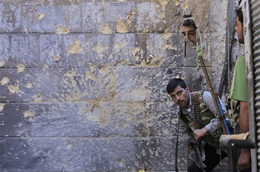 A Free Syrian Army soldier (right) looks through a mirror which helps him see Syrian troops from the other side, as he takes his position with his comrade during fighting, at the old city of Aleppo city, Syria on Monday, Sept. 24, 2012. Most of those fighting the regime of President Bashar Assad are ordinary Syrians and soldiers who have defected, having become fed up with the authoritarian government, analysts say. But increasingly, foreign fighters and those adhering to an extremist Islamist ideology are turning up on the front lines.