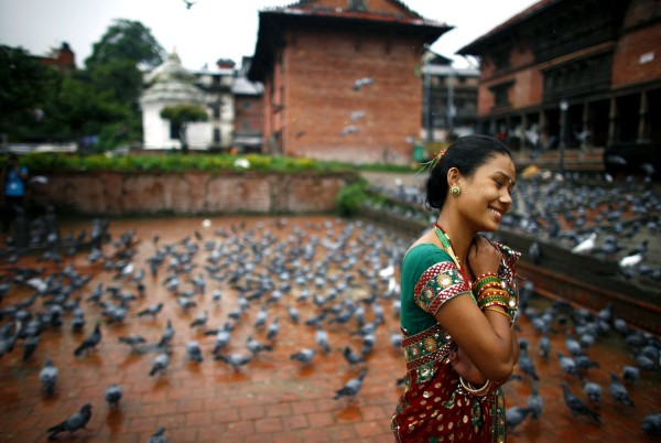 A Nepalese Hindu woman walks past pigeons after offering prayers at the Pashupatinath temple during Teej festival celebrations in Katmandu, Nepal, Tuesday, Sept. 18, 2012. During the festival, Nepalese Hindu women observe a daylong fast and pray for their husbands and for a happy married life. Those who are unmarried pray for a good husband.