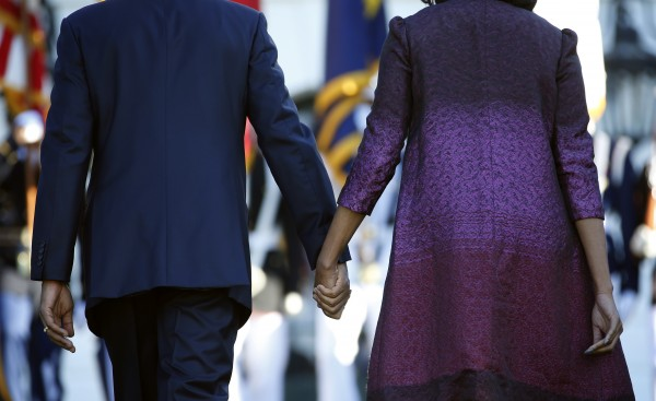 President Barack Obama and first lady Michelle Obama hold hands as they walk back to the White House in Washington on Tuesday, Sept. 11, 2012, after joining members of the White House staff during a moment of silence to mark the 11th anniversary of the Sept. 11.
