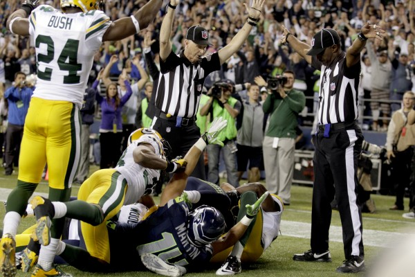 One official (left) signals a touchdown by Seattle Seahawks wide receiver Golden Tate, obscured, on the last play of an NFL game against the Green Bay Packers, Monday night, Sept. 24, 2012, in Seattle. The other official (right) is signaling a touch back. The Seahawks won 14-12.