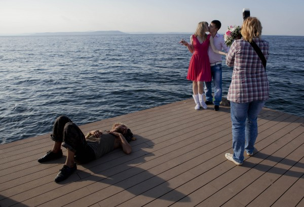 A couple poses for photos as a man sleeps on a pier in Vladivostok, Russia on Monday, Sept. 10, 2012.