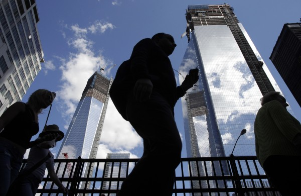 Visitors to the National September 11 Memorial walk below the rising towers at 1 World Trade Center (left( and 4 World Trade Center, Monday, Sept. 10, 2012 in New York. Tuesday will mark the eleventh anniversary of the attacks of Sept. 11, 2001.