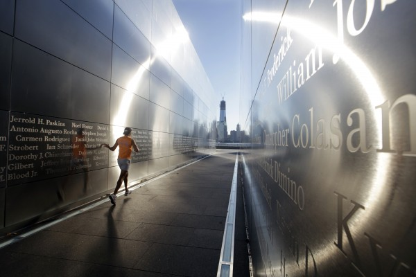 The construction of One World Trade Center, now up to 104 floors, is seen Tuesday, Sept. 11, 2012, across the Hudson River as a runner glides his hand at Liberty State Park in Jersey City, N.J.,  along the wall of 'Empty Sky,' New Jersey's memorial to the 749 people from the state lost during the  Sept. 11 terrorist attacks on the World Trade Center.  Americans paused again Tuesday to mark the 11th anniversary of the Sept. 11, 2001, terror attacks with familiar ceremonies, but also a sense that it's time to move forward after a decade of remembrance.