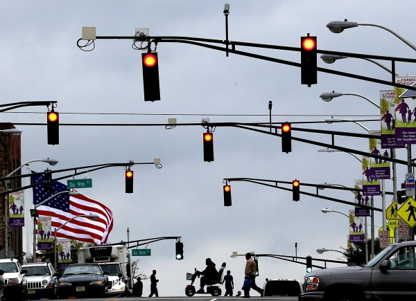 A large U.S. flag (left) waves in gusty winds and pedestrians cross the street under red streetlights in Newark, N.J. on Tuesday, Sept. 18, 2012. A tornado watch was issued for parts of New Jersey, New York City and New York's lower Hudson Valley until 7 p.m. The National Weather Service Storm Prediction Center says lightning, hail and wind gusts up to 70 mph are possible.