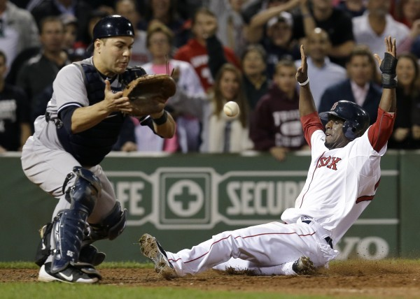 Boston Red Sox's Pedro Ciriaco slides in to score the winning run on a single hit by Jacoby Ellsbury as New York Yankees catcher Russell Martin, left, waits for the late throw during the ninth inning of a baseball game at Fenway Park in Boston, Tuesday, Sept. 11, 2012. The Red Sox won 4-3.