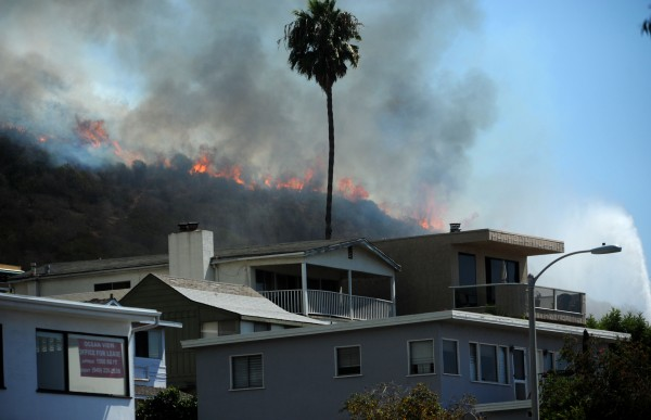 A wildfire looms above homes near Ruby's Diner on the Pacific Coast Highway in Laguna Beach, Calif., Sunday, Sept. 16, 2012. Fire crews are battling a 3-acre brush fire in south Laguna Beach at Pacific Coast Highway and Nyes Place, according to the Orange County Fire Department.