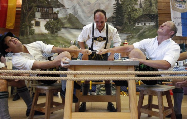A judge watches the leather ring held by two competitors with their middle fingers at the German Finger Wrestling Championships in in Warngau, Germany, Sunday, Sept. 16, 2012. Competitors battled for the title in this traditional rural sport where the winner has to pull his opponent over the marked line on the table.
