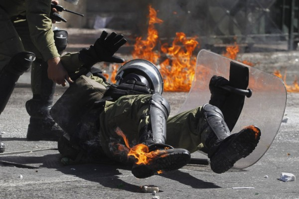 A riot policeman reacts after he was hit by a petrol bomb thrown by protesters during a nationwide general strike in Athens, Greece, Wednesday, Sept. 26, 2012. Police clashed with protesters hurling petrol bombs and bottles in central Athens Wednesday after an anti-government rally called as part of a general strike in Greece turned violent.