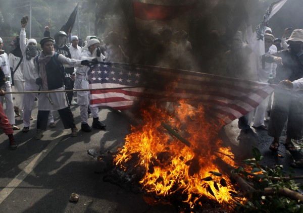 Muslim protesters burn a U.S. flag during a protest against American-made film &quotInnocence of Muslims&quot that ridicules Islam and depicts the Prophet Muhammad as a fraud, a womanizer and a madman, outside the U.S. Embassy in Jakarta, Indonesia, Monday, Sept. 17, 2012.