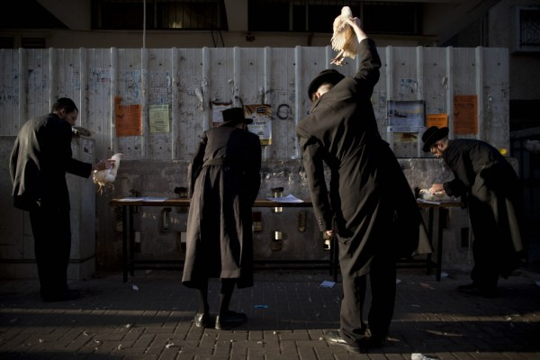 Ultra-Orthodox Jews swing chickens over their heads as part of the Kaparot ritual, in which it is believed that one transfers one's sins from the past year into the chicken, in the Ultra-Orthodox city of Bnei Brak near Tel Aviv, Israel, Tuesday, Sept. 25, 2012. The ritual is performed before the Day of Atonement, Yom Kippur, the holiest day in the Jewish year which starts at sundown Tuesday.
