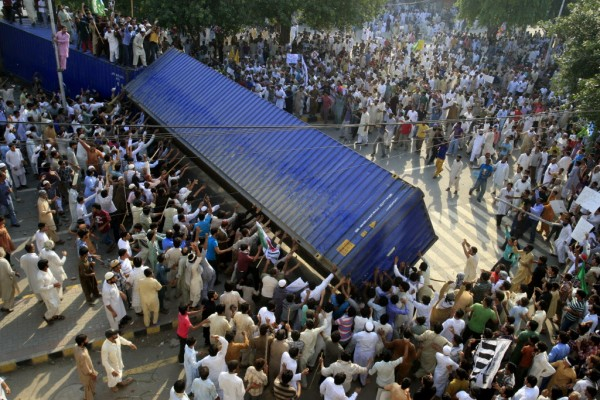 Pakistani protesters topple a shipping container police used to block the road to the U.S. consulate in Lahore, Pakistan on Friday, Sept 21, 2012. Tens of thousands protested around the country against an amateurish anti-Muslim film produced in the United States and vulgar caricatures of the Prophet Muhammad published in a French satirical weekly after the government encouraged peaceful protests and declared a national holiday — &quotLove for the Prophet Day.&quot Demonstrations turned violent in several Pakistani cities and more than a dozen people were killed and many more injured.