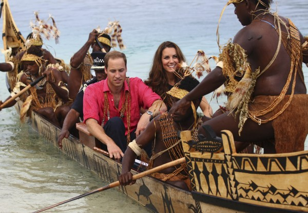 Britain's Prince William and his wife, Kate, the Duke and Duchess of Cambridge, arrive in Tavanipupu, Solomon Islands, on a traditional war canoe Monday, Sept. 17, 2012.