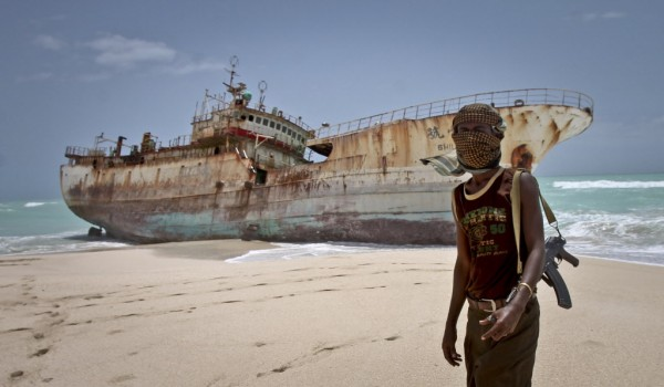 Masked Somali pirate Abdi Ali stands near a Taiwanese fishing vessel that washed up on shore after the pirates were paid a ransom and released the crew, in the once-bustling pirate den of Hobyo, Somalia. The empty whisky bottles and overturned, sand-filled skiffs that litter this shoreline are signs that the heyday of Somali piracy may be over -- most of the prostitutes are gone, the luxury cars repossessed, and pirates talk more about catching lobsters than seizing cargo ships.
