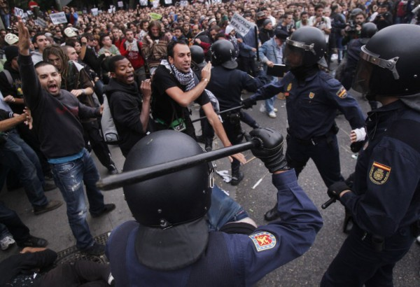 Protestors clash with the police riots during the march to the parliament against austerity measures announced by the Spanish government in Madrid, Spain, Tuesday, Sept. 25, 2012. Spain's Parliament has taken on the appearance of a heavily guarded fortress with dozens of police blocking access from every possible angle, hours ahead of a protest against the conservative government's handling of the economic crisis. The demonstration, organized behind the slogan 'Occupy Congress,' is expected to draw thousands of people.