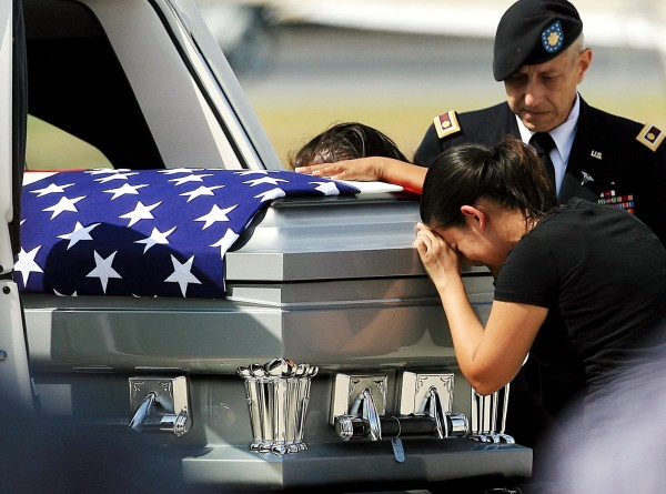Liliana Montenegro cries over the casket of her brother U.S. Army Warrant Officer Jose Luis Montenegro Jr. after his body arrived Sunday, Sept. 16, 2012, at McCreery Aviation in McAllen, Texas. Montenegro was stationed at Fort Bragg, N.C. and was serving his third tour of duty overseas when his helicopter was shot down in Afghanistan's Logar province. Nearly 2,000 American troops have been killed in the conflict since the 2001 invasion.
